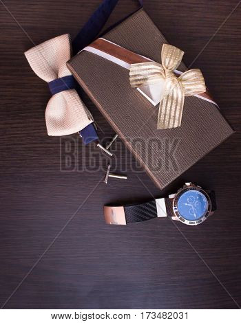 Genuine accessories as a gift to the man on brown background