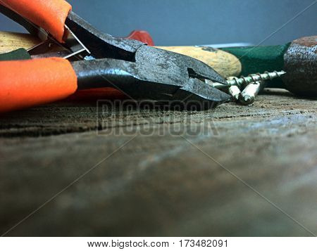close up of orange set of pliers with defocused foreground