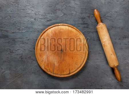 Wooden board with a rolling pin on the dark stone surface top view