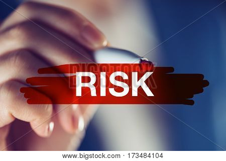 Risk in business concept businesswoman marking the word with red highlighting marker pen