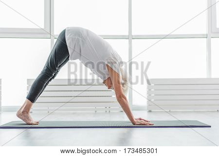 Calm old woman is undergoing exercise. She is bending her back down while standing in position