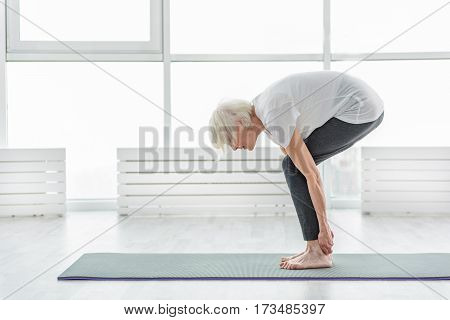 Healthy mature lady is doing workout at gym. She standing in position and touching heels by hands