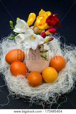 yellow, red. white freesia in a ceramic vase on a background of colored Easter eggs on black background