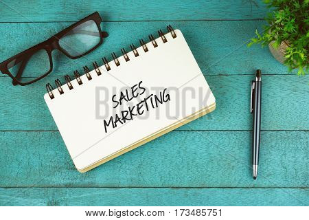 Business Concept. Top view of eye glasses, plant, pen and open notebook written with Sales Marketing on blue wooden background.