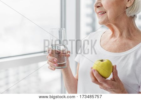 Healthy lifestyle gives long life. Happy old woman is eating apple and drinking water. She is standing near window and smiling