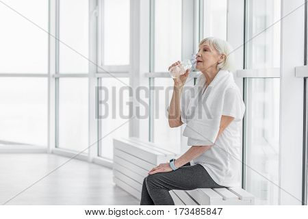 Relaxed old woman is drinking water from bottler. She is sitting on windowsill and relaxing after exercising
