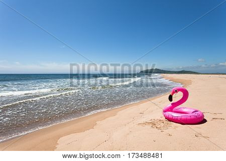 Inflatable pink flamingos on the desertted sand beach.