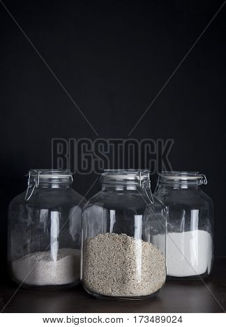 Three huge glass jars with oatmeal and flower on dark black background