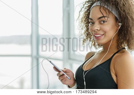 Smiling mulatto girl is standing near window. She holding smartphone and looking at camera with interest