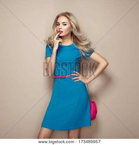 Blonde young woman in elegant blue summer dress. Girl posing on a beige background. Jewelry and hairstyle. Girl with handbag. Fashion photo
