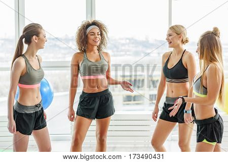 Cheerful smiling girl are standing in light gym. They talking to each other
