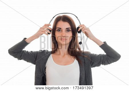 young serious girl looks straight and keeps hands for headsets is isolated on a white background