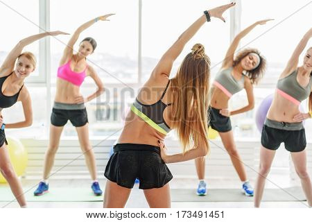 Slim happy women are doing exercise together. They rising hand up and making incline