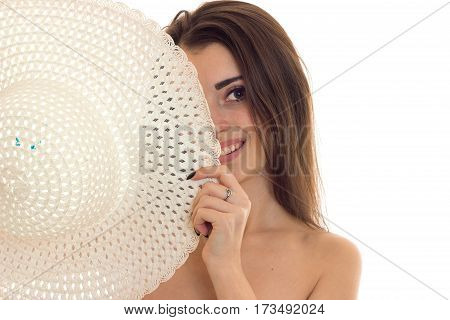 beautiful smiling girl covering her face a close-up of hat isolated on white background