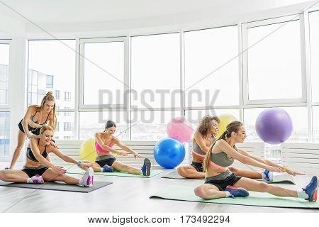 Smiling slim girls are sitting on mats. They doing exercise. Cheerful female coach is helping them