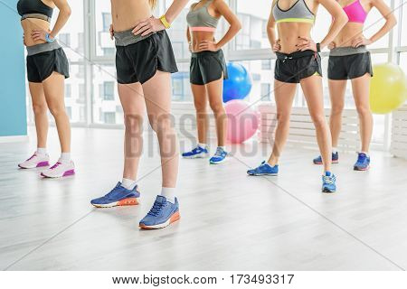 Sportive girls with slender legs in sneakers are standing near big window. They holding arms on belt
