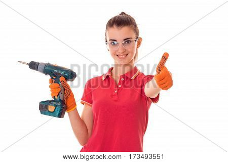 joyful young girl in a red t-shirt and transparent protective glasses shows class and holding a drill is isolated on the b