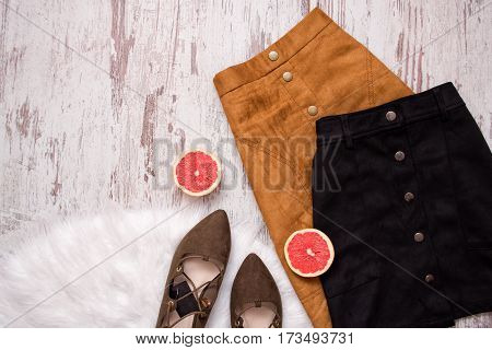 Brown and black suede skirt brown suede shoes cut grapefruit halves. Wooden background. Fashion concept. top view