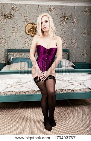 sexy beautiful blonde woman in corset and stockings standing beside the bed.