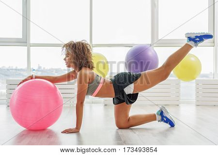 Slim active young woman is kneeling near pink ball and doing exercise. She looking ahead