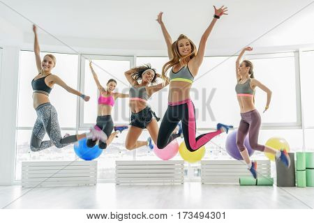 Hilarious sportive girls are jumping in light gym. They are laughing merrily