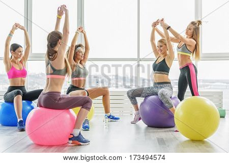 Smiling slim taut girls are sitting on balls and rising hands up. Female coach helping them