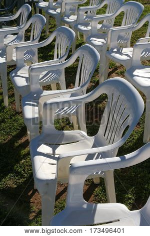 Two rows of white, stackable plastic patio chairs casting shadows set up for an event.