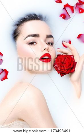 High Fashion model girl taking milk bath, spa and skin care concept. Beauty young Woman with bright makeup and red rose flower relaxing in milk bath. Skincare
