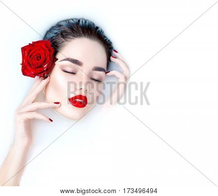 Beautiful Fashion model girl taking milk bath, spa and skin care concept. Beauty young Woman with bright makeup and red rose flower relaxing in milk bath. Healthy Face and hands, red nails and lips.