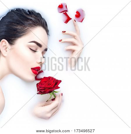 Beautiful Fashion model girl taking milk bath, spa and skin care concept. Beauty young Woman with bright makeup and red rose flower relaxing in milk bath. Healthy Face and hands, red nails and lips
