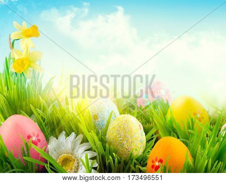 Easter nature spring scene background. Beautiful colorful eggs in spring grass meadow over blue sky with sun. Invitation card border design