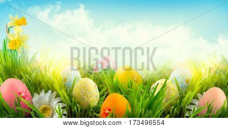 Easter nature spring scene background. Beautiful colorful eggs and flowers in spring grass meadow over blue sky with sun. Invitation card border design