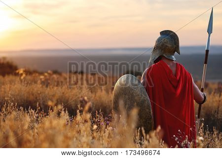 Victorious warrior. Rearview shot of a legionary roman soldier in a red cape and a helmet standing in the field on beautiful dusk stunning scenery on the background copyspace confidence peace calm