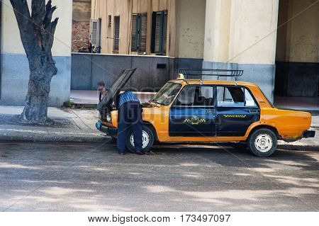 Havana, Cuba, July, 11, 2006. - A taxi man getting under the hood of his old Lada in Havana city. Cubans have become best mechanics in the world by keeping their cars running with no parts available.