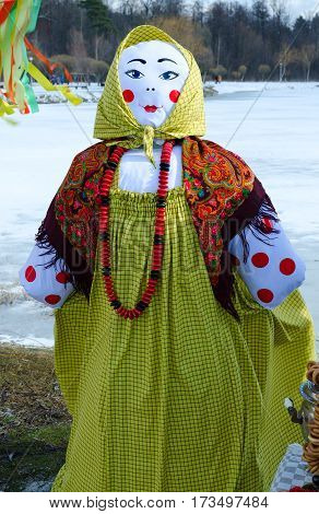 Shrovetide doll in colorful headscarf and sarafan with large beads on neck