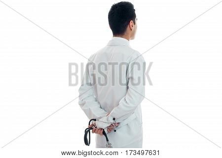 portrait from behind of young brunette man doctor in unifrom with stethoscope in his hands isolated on white