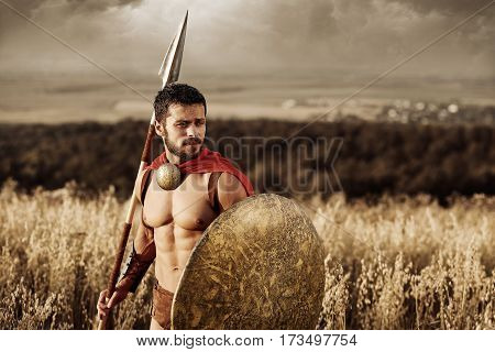 Young and fearless. Sepia shot of a young brave Spartan warrior standing alone in a field copyspace  legionnaire gladiator bravery sportive athletic muscles strong perfection medieval concept