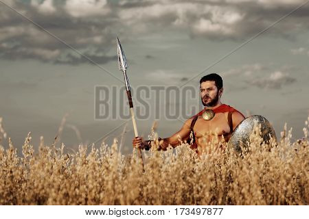 Brave young warrior. Handsome young muscular legionnaire holding a spear and a sword posing against gloomy skies in the field copyspace strength bravery ancient weapon war peace calamity concept