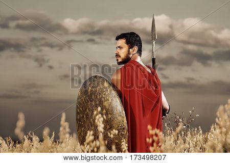 Medieval hero. Sepia toned shot of a young male Greek or Roman warrior walking in the field with a spear and a shield looking around copyspace bravery fearless hero fighter battlefield peace concept