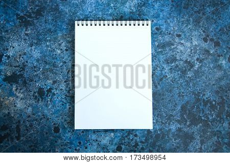 Empty white page of notebook on a blue textured background