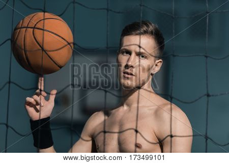 portrait of sporty man holding basketball ball on finger