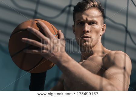 portrait of focused sporty man holding basketball ball
