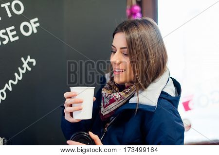 Young woman in a coffee shop holding a to go cup with coffee enjoying the flavor.