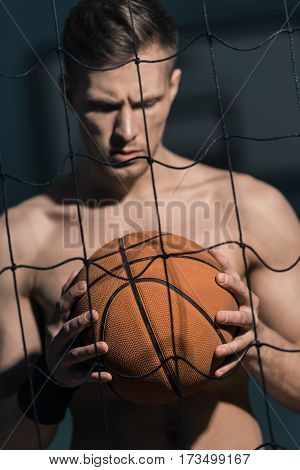 portrait of sporty man looking at basketball ball in hands
