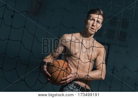 portrait of emotional sporty man holding basketball ball