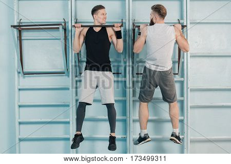 sporty men exercising on sport equipment in gym