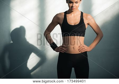 portrait of sporty woman in sportive clothes with shadows