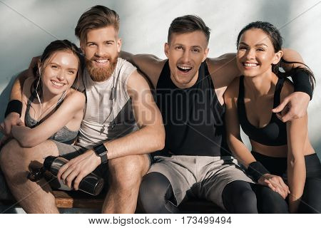 portrait of smiling sporty men and women sitting on bench in gym