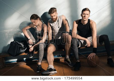 tired smiling sporty men and woman sitting on bench in gym