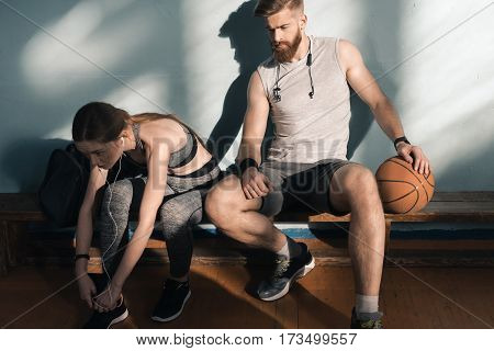 sporty woman tying shoelaces with man sitting on bench near by